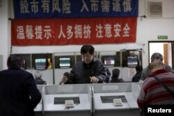 FILE - Investors look at computer screens showing stock information on the first trading day after the week-long Lunar New Year holiday at a brokerage house in Shanghai, China, Feb. 15, 2016.
