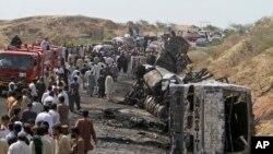 Người Pakistan tụ tập gần đống đổ nát của các chiếc xe bị phá hủy trong tai nạn giao thông gần Gadani, Pakistan, 22/3/2014