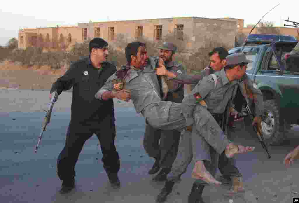 Afghan security personnel assist an injured police after a suicide car bombing and a gunfight near the U.S. consulate in Herat, Afghanistan, Sept. 13, 2013.