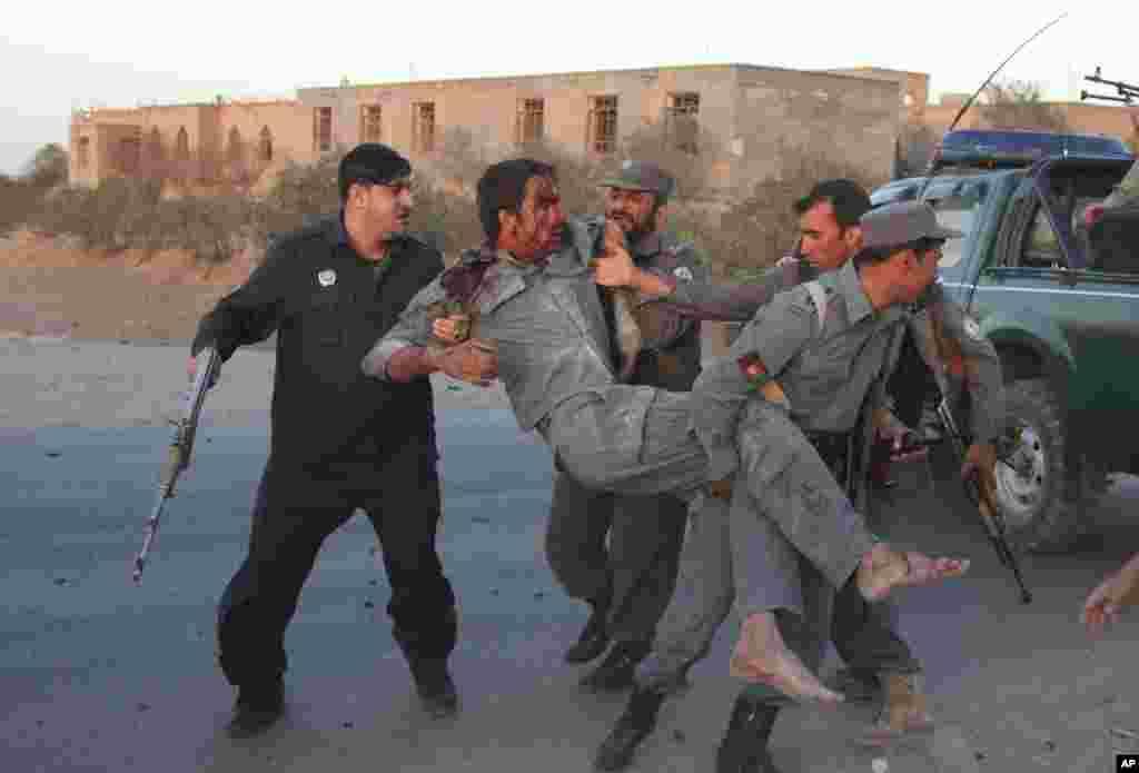 Des membres des forces de sécurité afghanes aidant un policier blessé dans l'attentat