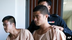 Myanmar migrants Win Zaw Htun, right, and Zaw Lin, left, are escorted by officials after their guilty verdict at court in Koh Samui, Thailand. The head of Myanmar's military has joined growing criticism on Dec. 27, 2015, of the death sentences Thailand to two men for a double murder on a resort island.