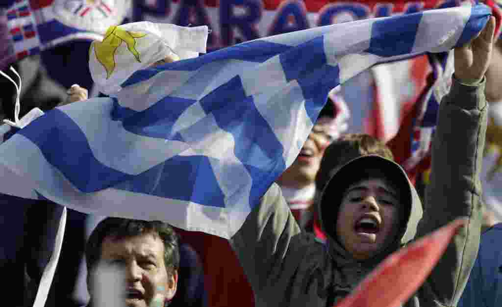 A fan waves an Uruguayan flag before the Copa America final soccer match between Uruguay and Paraguay in Buenos Aires, Argentina, Sunday, July 24, 2011. Uruguay is trying to become the tournament's most successful team, while Paraguay is looking to prove