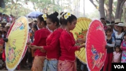 Dancers holding umbrellas in Siem Reap during the Khmer New Year celebration.
