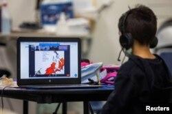 Daniel (5) menonton Dr. Seuss saat berlangsungnya kelas online melalui zoom di Westchester Family YMCA di tengah pandemi COVID-19 in Los Angeles, California, 2 Maret 2021.