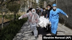 In this March 30, 2020 file photo, people wearing protective clothing carry the body of a victim who died after being infected with the new coronavirus at a cemetery just outside Tehran, Iran. (AP Photo/Ebrahim Noroozi, File)