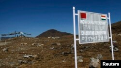 FILE - A signboard is seen from the Indian side of the Indo-China border at Bumla, in the northeastern Indian state of Arunachal Pradesh.