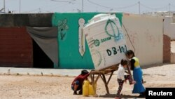 Syrian refugees children collect water at the Al-Zaatari refugee camp in Mafraq, Jordan, near the border with Syria, May 30, 2016.
