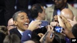 Barack Obama sourit pour les caméras après un meeting à Columbus, Ohio, le 5 nov. 2012