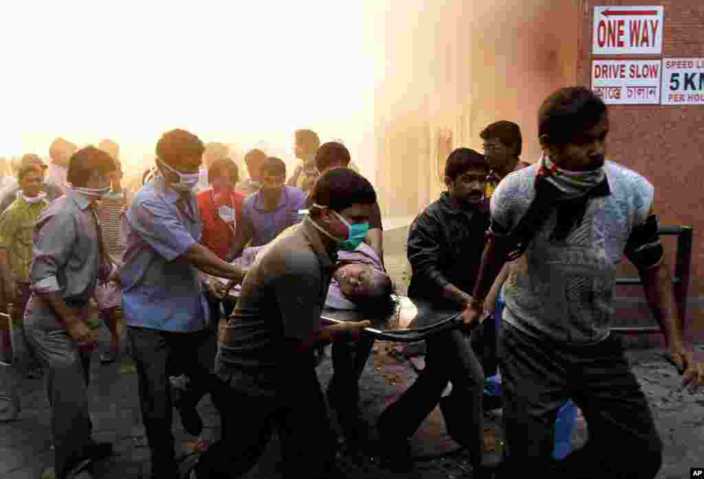People help evacuate patients after a fire broke out at a hospital in Kolkata, India, Friday, Dec. 9. The fire swept through the multistory hospital in eastern India early Friday, trapping residents in the smoke-filled building. (AP/Bikas Das)