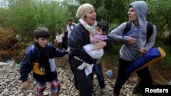 FILE - Migrants cry and walk towards Gevgelija in Macedonia after crossing Greece's border, Macedonia.