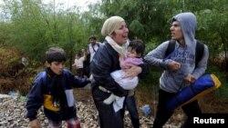 非法移民一边哭泣一边穿过希腊边界马其顿。