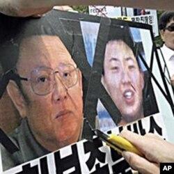韩国活动人士划开金正日像 示威者说右侧为金正银