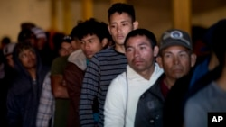 Honduran migrants stand in line for breakfast inside an empty warehouse that opened its doors to migrants in downtown Tijuana, Mexico, Dec. 18, 2018. Two teens from Honduras were killed in Tijuana while waiting to apply for asylum in the U.S.