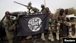 Tentara Nigeria memegang bendera Boko Haram bahwa mereka telah ditangkap di kota yang baru-baru ini direbut kembali dari Damasak, Nigeria, 18 Maret 2015 (Foto: dok)
