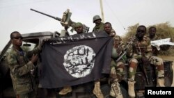 FILE - Nigerian soldiers hold up a Boko Haram flag that they had seized in the recently retaken town of Damasak, Nigeria.