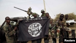 FILE- Nigerian soldiers hold up a Boko Haram flag that they had seized in the recently retaken town of Damasak, Nigeria.
