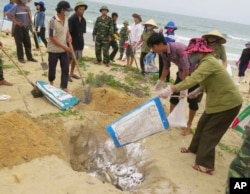 FILE- Villagers bury dead fish on a beach in Quang Binh, Vietnam.