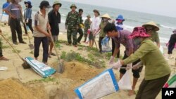 FILE- In this April 28, 2016, file photo, villagers bury dead fish on a beach in Quang Binh, Vietnam. Toxic waste discharged from a Taiwanese-owned Formosa Plastics Group steel complex unit in central Vietnam harmed the livelihoods of more than 200,000 people, including 41,000 fishermen, the Vietnamese government said on Friday in tallying the damage from what it has called the country's worst environmental disaster according to local media. The company has pledged to pay $500 million in compensation.