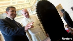 FILE - Pope Francis exchanges gifts with Peru's President Ollanta Humala during a private audience at the Vatican, Nov. 14, 2014.