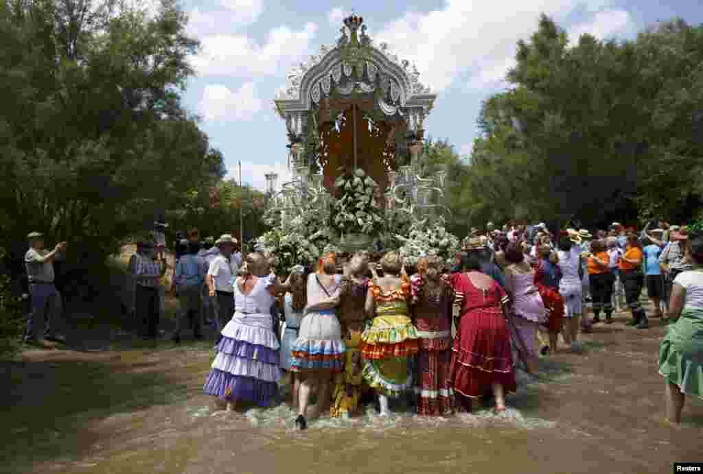 Para peziarah mendorong kereta melewati Sungai Quema menuju kuil El Rocio di Aznalcazar, Spanyol selatan.