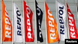 FILE - Repsol flags are seen at a conference hall during the company's annual shareholders meeting in Madrid, Spain, May 19, 2017.