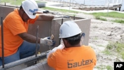 Construction workers build a composite-block wall at a project in Texas. (Photo courtesy of PRNewsFoto/Bautex Systems)