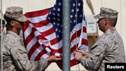 FILE - U.S. officials say they'll discard plans to draw down troop strength to 5,500 by year's end in Afghanistan. Here, U.S. Marines lower their flag during a handover ceremony, as the last U.S. Marines unit and British combat troops end their Afghan operations in Helmand, Oct. 26, 2014.