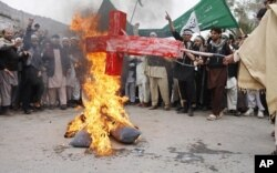 Des Afghans brûlent une photo du président Barack Obama lors d'une manifestation à Jalalabad (13 mar 2012)