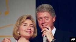 In this June 22, 1994 file photo, President Bill Clinton and first lady Hillary Clinton for supporters in Washington. (AP