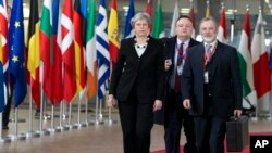 British Prime Minister Theresa May, left, arrives for an EU summit at the Europa building in Brussels, March 23, 2018.