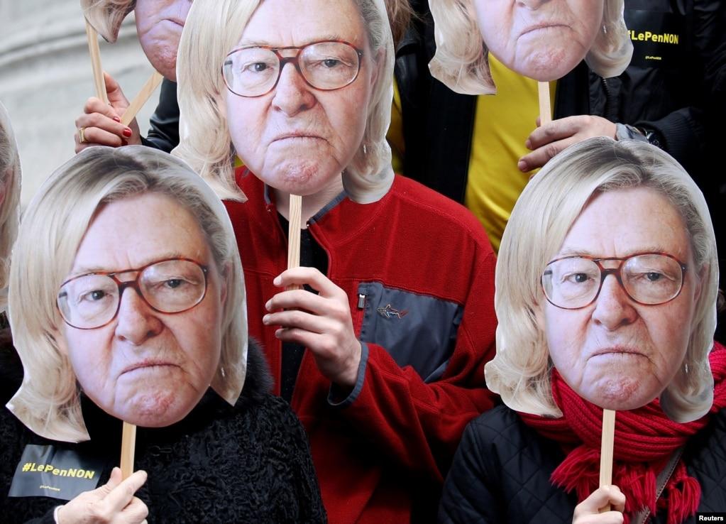 """在五一國際勞動節遊行中,巴黎的活動人士們帶著印有法國極右派政黨""""國民陣線""""創始人讓-馬里·勒龐頭像的面具。 在面具上,勒龐留著與他女兒同樣的髮型。 勒龐代表""""國民陣線""""參加了2017年法國總統選舉。"""