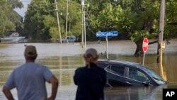 Warga setempat mengamati banjir yang menggenangi jalan Old Jefferson Highway di Bayou Manchac, Prairieville, Louisiana, 16 Agustus 2018 (AP Photo/Max Becherer).