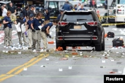 FILE - Federal Bureau of Investigation (FBI) officials label and collect evidence near the site of an explosion which took place on Saturday night in the Chelsea neighborhood of Manhattan, New York, Sept. 18, 2016.