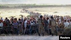 Người Kurd ở Syria chạy tránh nhóm Nhà nước Hồi giáo đứng chờ sau hàng rào biên giới Syria và Thổ Nhĩ Kỳ, để qua biên giới, 18/9/14