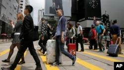 FILE - Mainland Chinese tourists carry suitcases as they walk at a shopping district in Hong Kong, April 12, 2015.