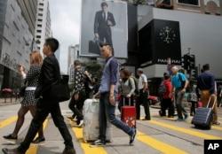 Những du khách Trung Quốc đại lục mang theo vali khi đi bộ tại một khu mua sắm ở Hong Kong, ngày 12 tháng 4 năm 2015.