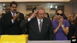 ປະທານາທິບໍດີ Raul Castro ພວມຄຳນັບ ຂະນະທີ່ທ່ານ ຢືນຢູ່ໃກ້ໆສົບ ຂອງມື້ລາງປະທານາທິບໍດີ Hugo Chavez ທີ່ນຳໄປດອຍໄວ້ຢູ່ໂຮງຮຽນນາຍຮ້ອຍແຫ່ງນຶ່ງ ໃນກຸງກາຣາກາສ (7 ກຸມພາ 2013)