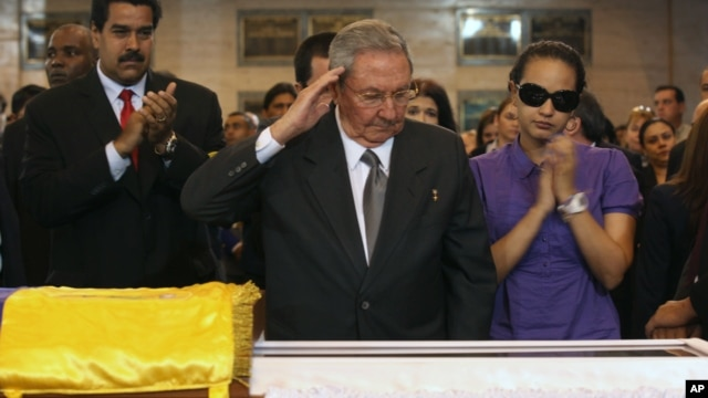 In this photo released by Miraflores Press Office,  Cuba's President Raul Castro salutes as he stands next to the coffin of Hugo Chavez at a military academy in Caracas, March 7, 2013.