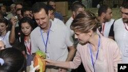 Suriya rahbari Bashar al-Assad va uning rafiqasi Asma poytaxt Damashqda Hims ahli uchun insonparvarlik yordamini taxlamoqda, 16-aprel, 2012-yil