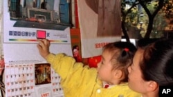A girl in her mother's arms touches a 1997 calender printed with pictures of Hong Kong sceneries Tuesday, Dec. 24, 1996 in Nanning, capital of Guangxi Zhuang Autonomous Region. Calenders concerning with Hong Kong sceneries became best seller at the year e