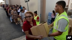 Doris Martínez receives supplies and water from municipal staff outside the City Hall in Morovis, Puerto Rico, Dec. 21, 2017. Over 30,000 residents of that mountain town wait for the restoration of electric power service, one of the last municipalities of Puerto Rico that remains completely in the dark more than three months after the passage of Hurricane Maria.