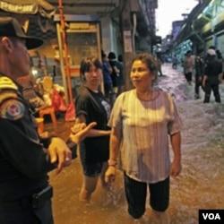 Warga berbincang-bincang dengan seorang polisi di tengah-tengah naiknya level air rendaman di daerah pusat kota Bangkok, Rabu (26/10).