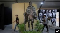 گاندھی کے 150 ویں جنم دن کے موقع پر لوگ ان کے مجسمے کے قریب سے گذر رہے ہیں