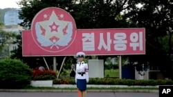 "Seorang polisi lalu lintas Korea Utara berdiri di depan slogan propaganda: ""Menjaga dengan sikap laksanakan-atau-mati di Pyongyang. (Foto:dok)"