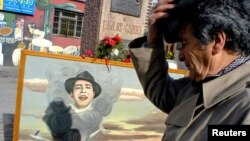 Un ¨fan¨de Carlos Gardel rinde tributo ante el monumento del cantante en Montevideo. Una partida de nacimiento encontrada en Toulouse prueba que Gardel nació en Francia, no en Argentina o en Uruguay como se creía.