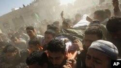 巴勒斯坦人周日抬着被以军空袭打死的人,为其举行葬礼