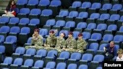 Tentara Inggris duduk di deretan kursi penonton yang kosong saat menyaksikan pertandingan babak penyisihan cabang olah raga senam putri di arena Greenwich utara Olimpiade London 2012 (29/7).
