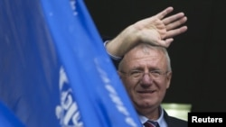 FILE - Serbian nationalist leader Vojislav Seselj waves to his supporters from a balcony of his Serbian Radical Party headquarters in Belgrade, Serbia, Nov. 12, 2014