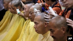 Pro-democracy activists get their heads shaved to protest against China's legislature, during a ceremony in Hong Kong, Sept. 9, 2014.