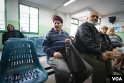 In a waiting room in a UNRWA clinic in southern Beirut, Palestinians Ahmad Said, second from left, and Abed Ghosein, third from left, await treatment. (J. Owens/VOA)